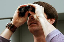 A man looks through binoculars